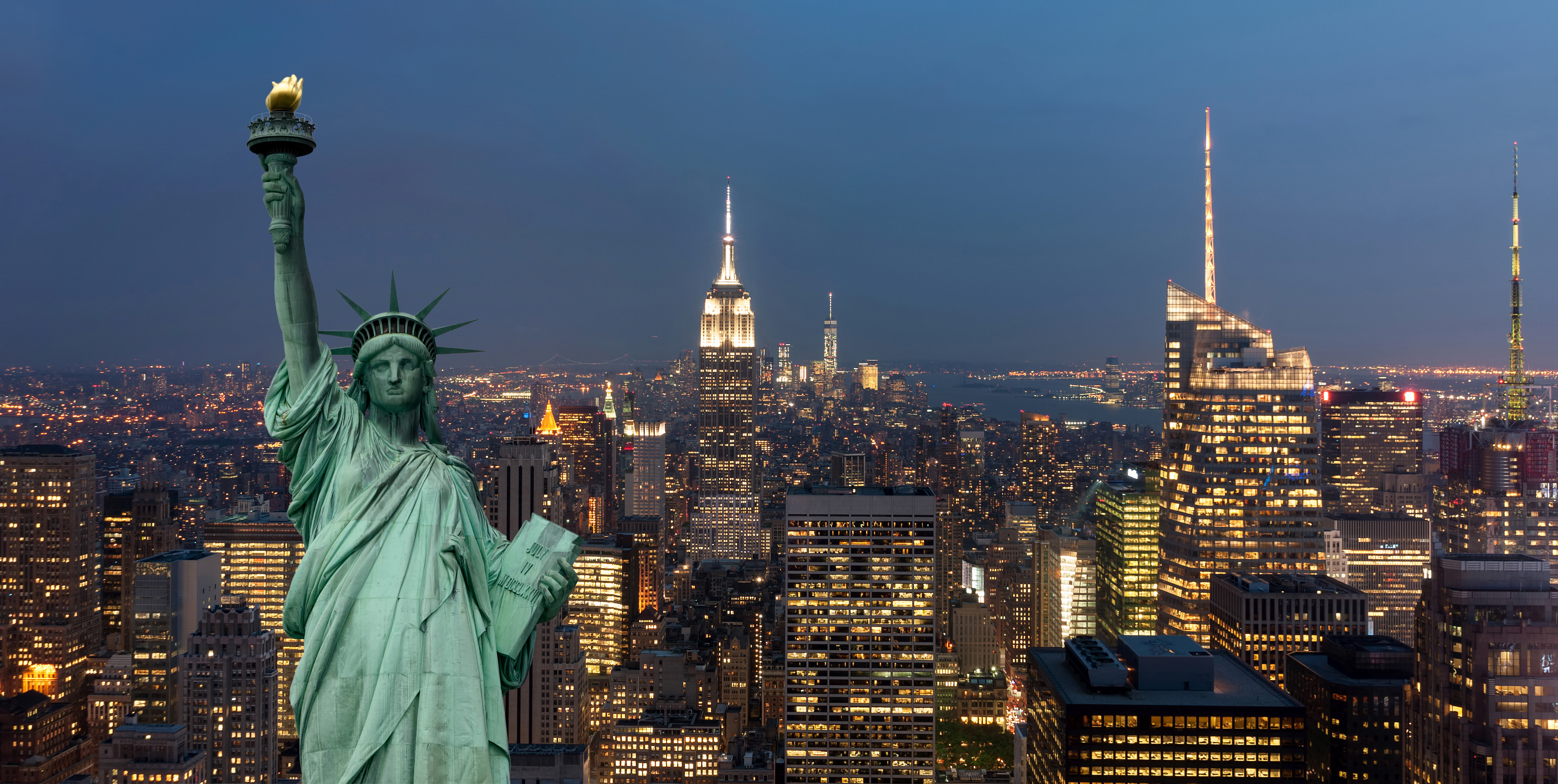 United States of America concept with statue of liberty in front of the New York cityscape at night